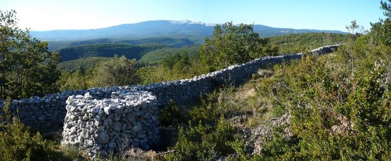 Il panorama che si apre sui monti del Vaucluse in direzione del Ventoux. In primo piano, una garitta davanti al muro della peste - Foto © Lacaille