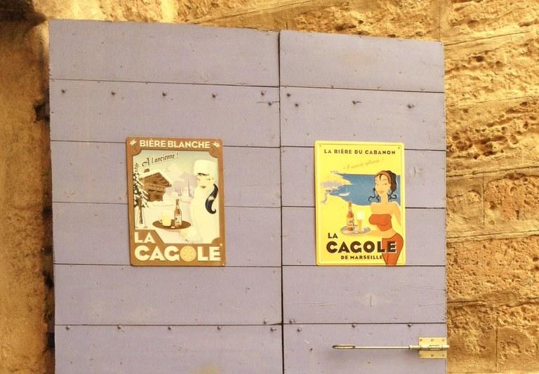 Vecchie pubblicità della birra La Cagole su una porta del Panier a Marsiglia